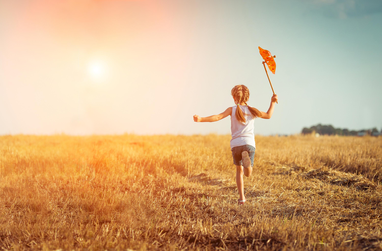 Kleines Mädchen mit Windrad rennt auf trockener Wiese