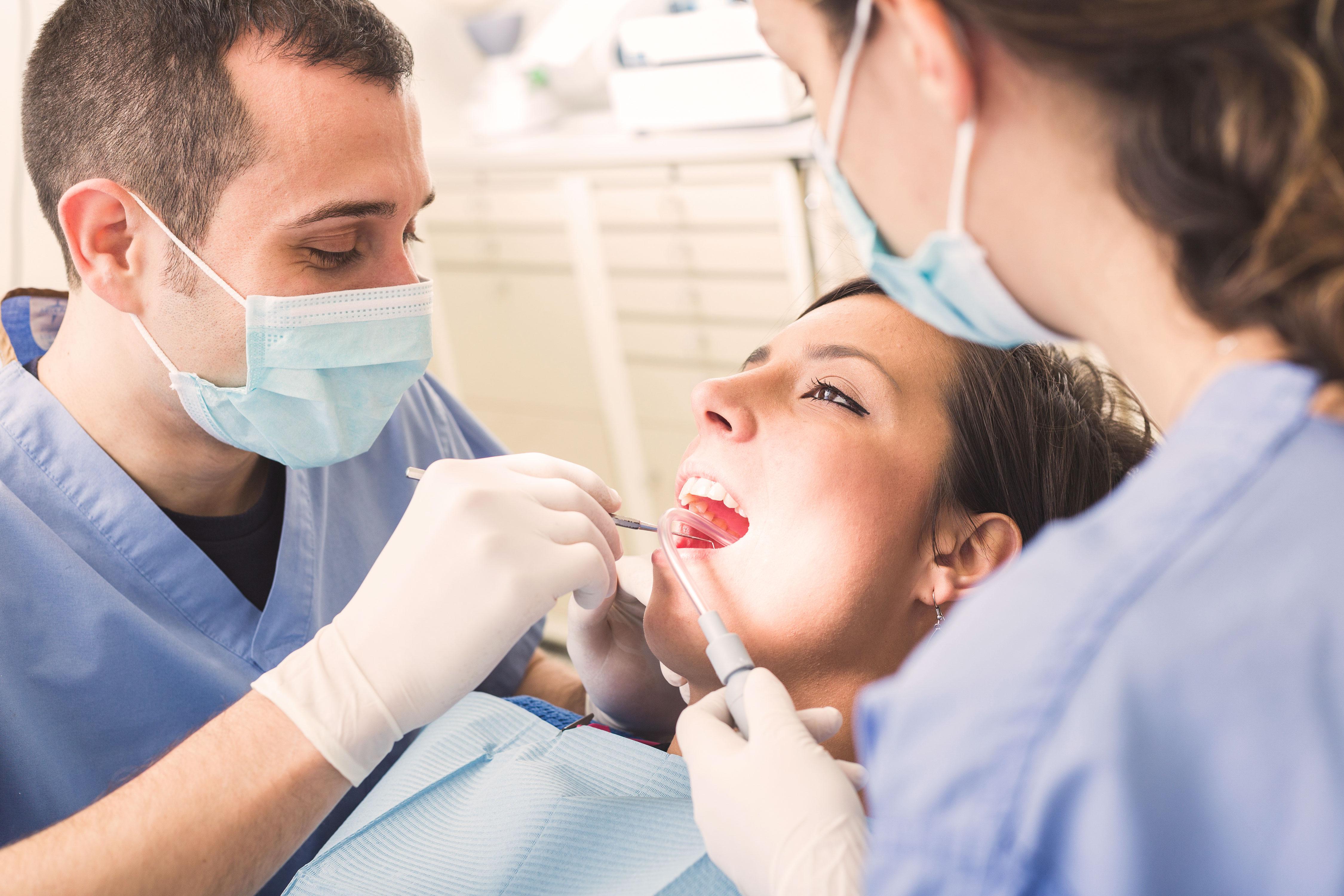 Zahnarzt und Zahnarzthelferin untersuchen die Zähne einer Patientin