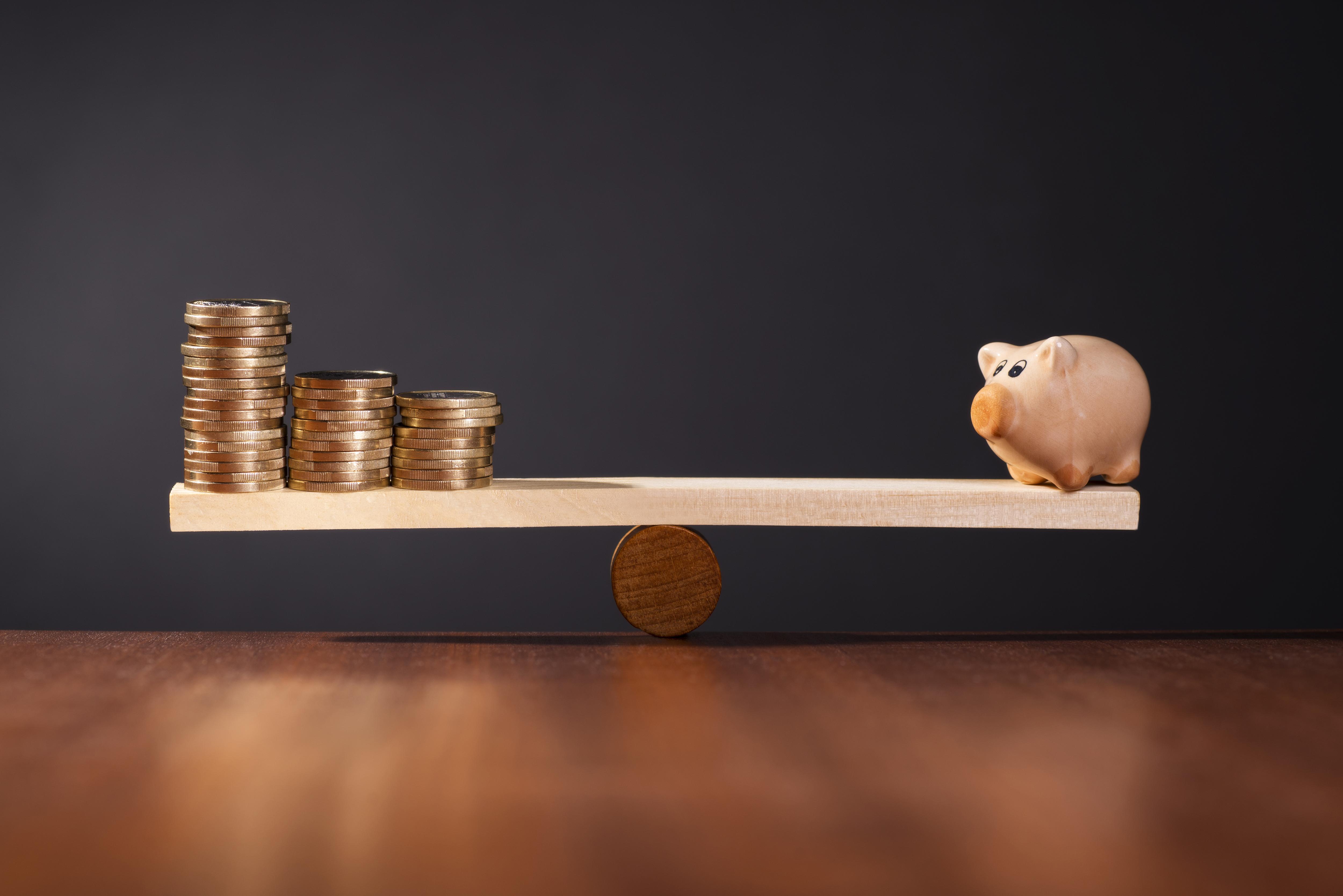 Sparschwein und Münzenstapel auf ausbalancierter Wippe als Symbol für eine sichere Geldanlage