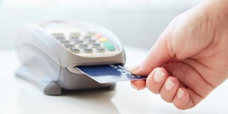 Frau zahlt mit Karte am Kartenlesegerät