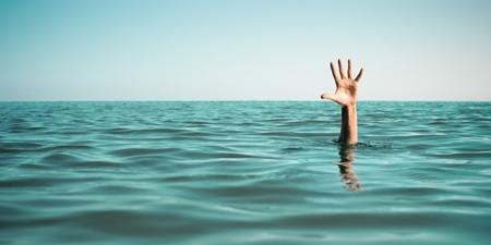 Hand eines Ertrinkenden ragt aus dem Meer
