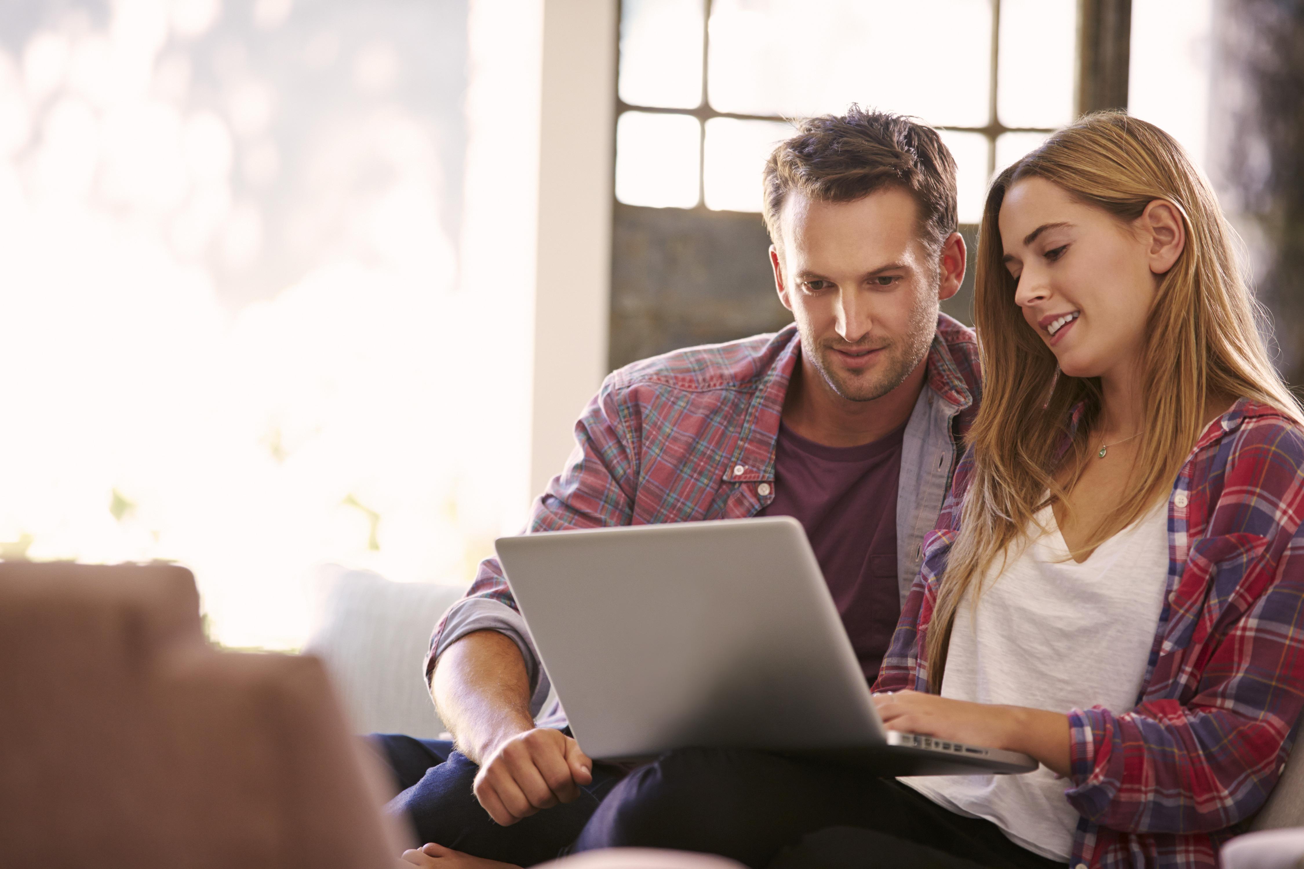 Junges Paar im offenen Zuhause vor dem Laptop