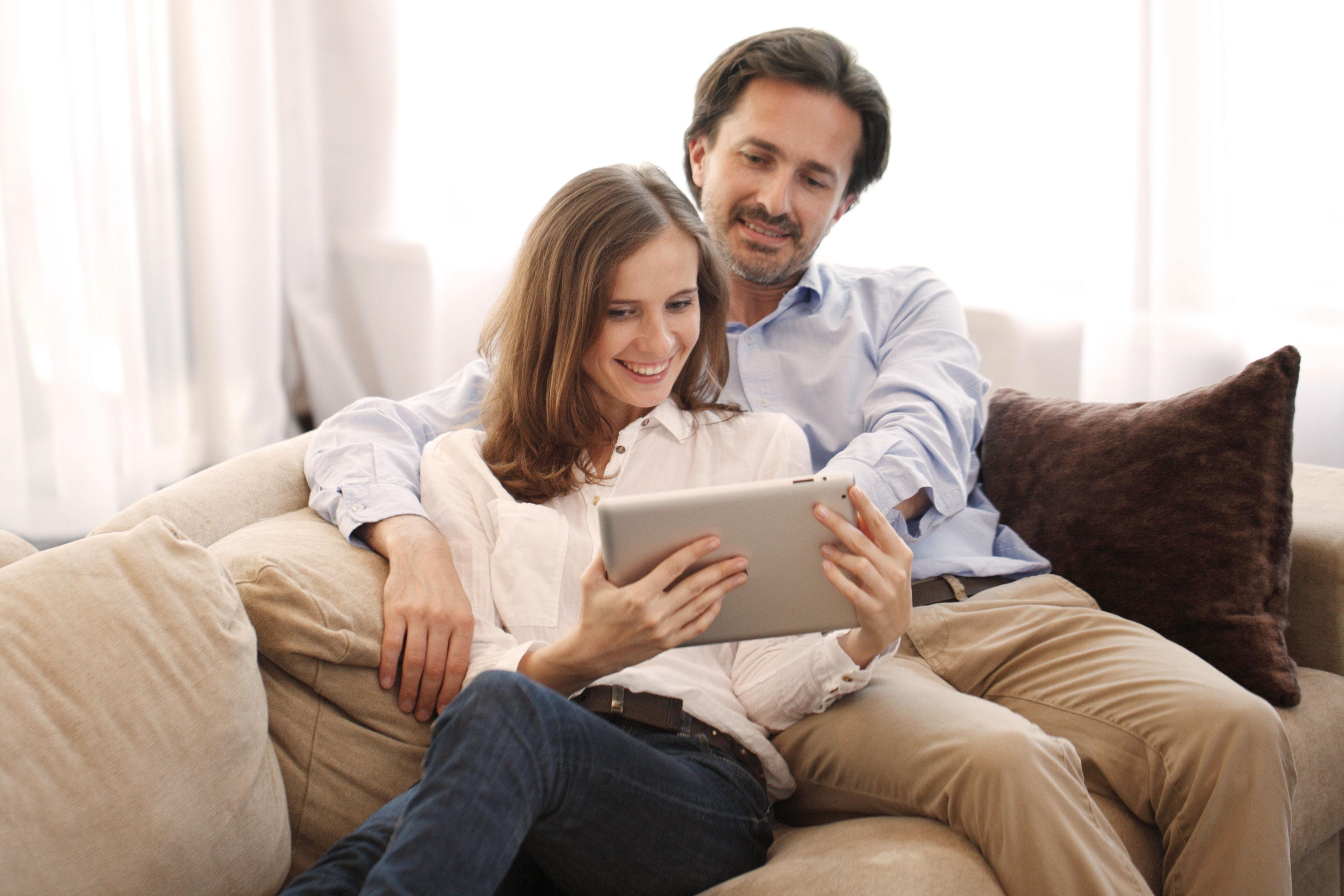 Lächelndes Paar auf dem Sofa vor dem Tablet