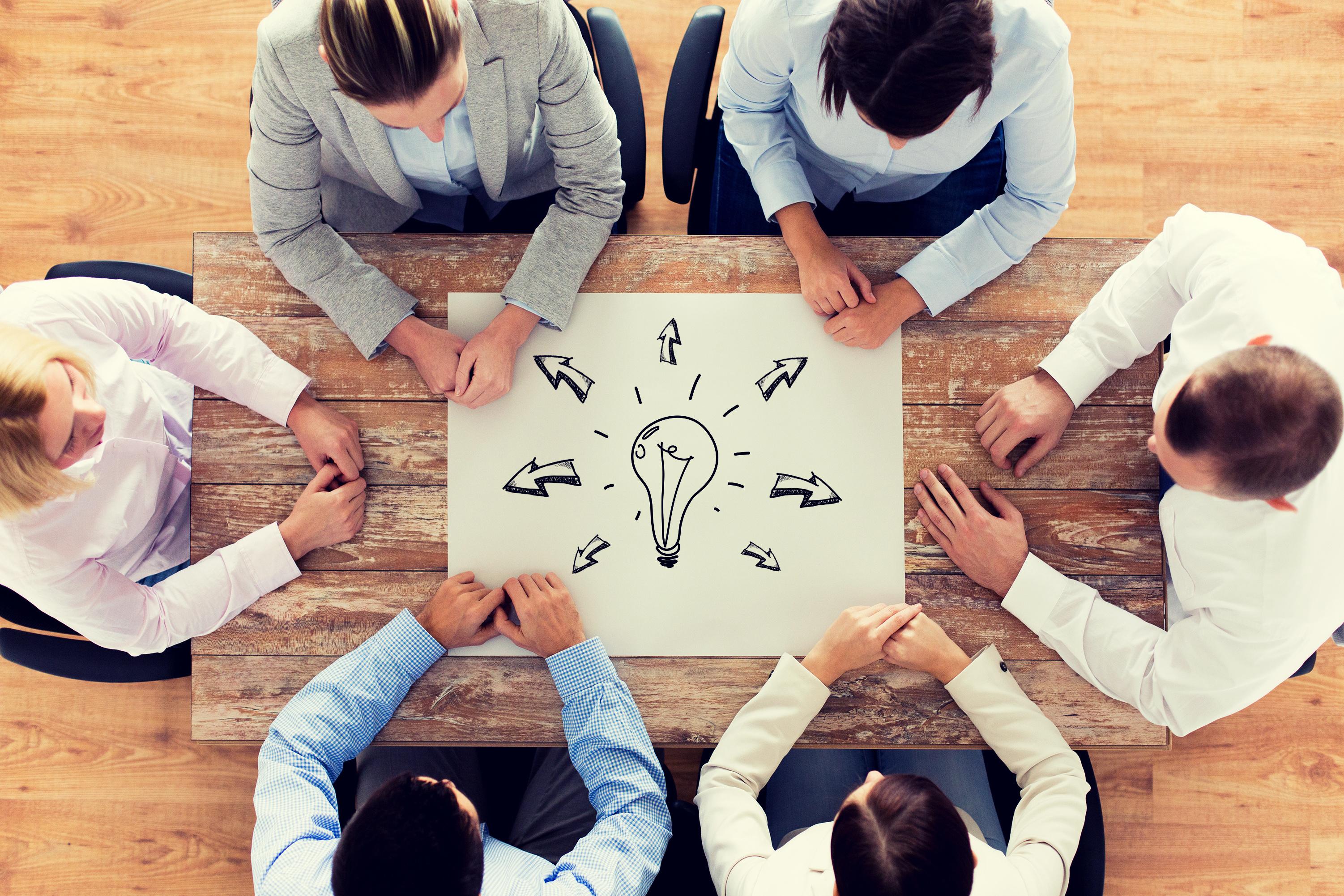 Businessmeeting vor Glühbirnen-Grafik an Holztisch