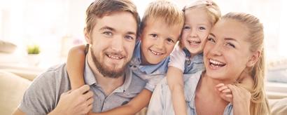 Junge lachende Familie in Umarmung auf dem Sofa