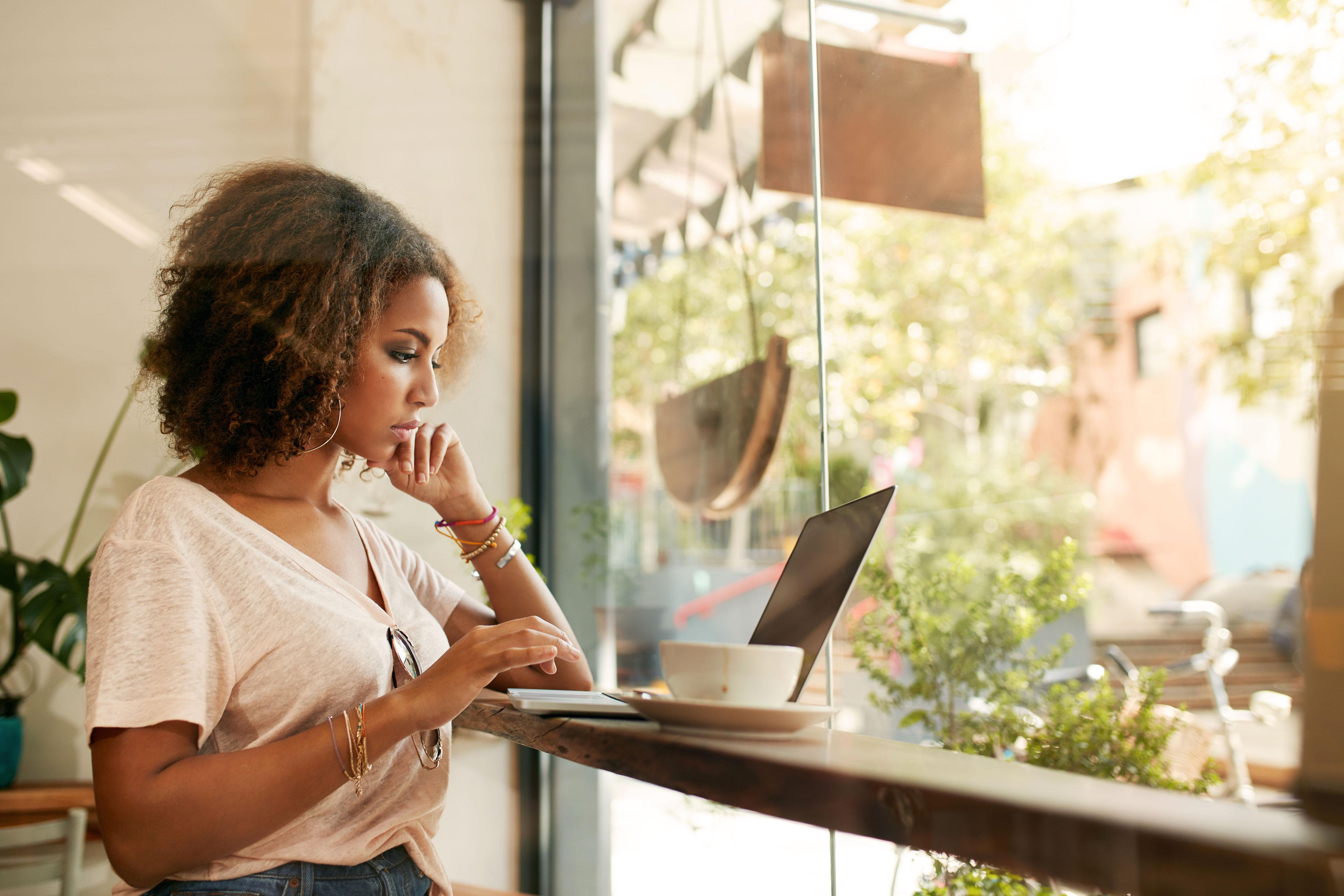Junge Frau nutzt ihren Laptop im Café