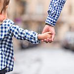 Mann nimmt Mädchen bei der Hand