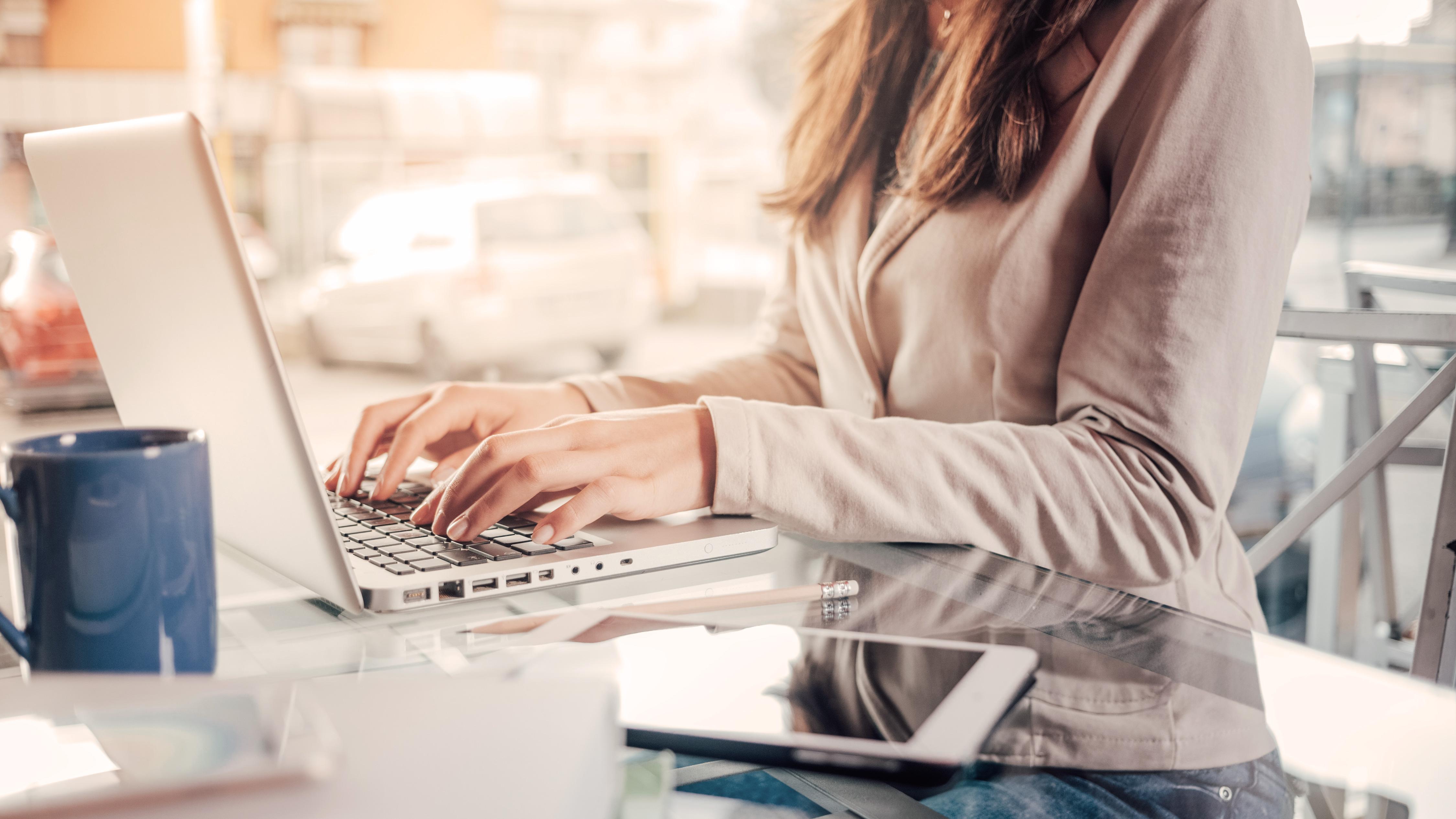 Frau im Close-up am Schreibtisch an ihrem Laptop
