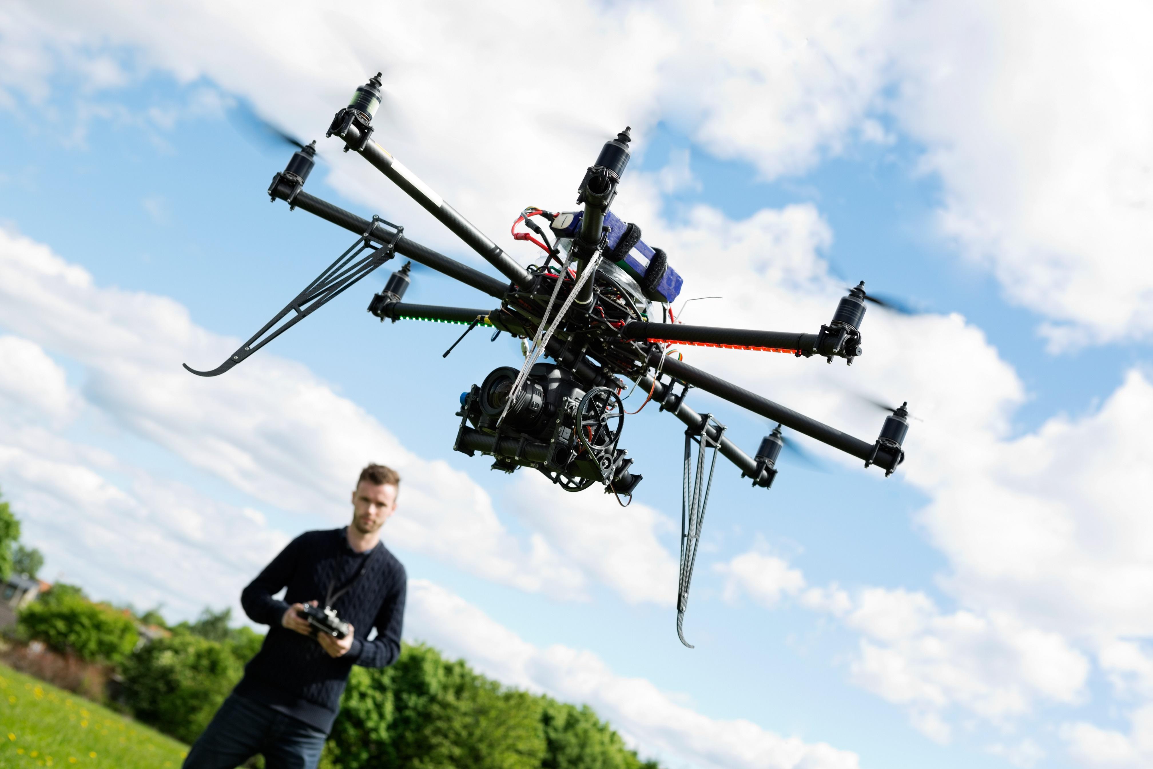 Junger Mann mit fliegender Drohne