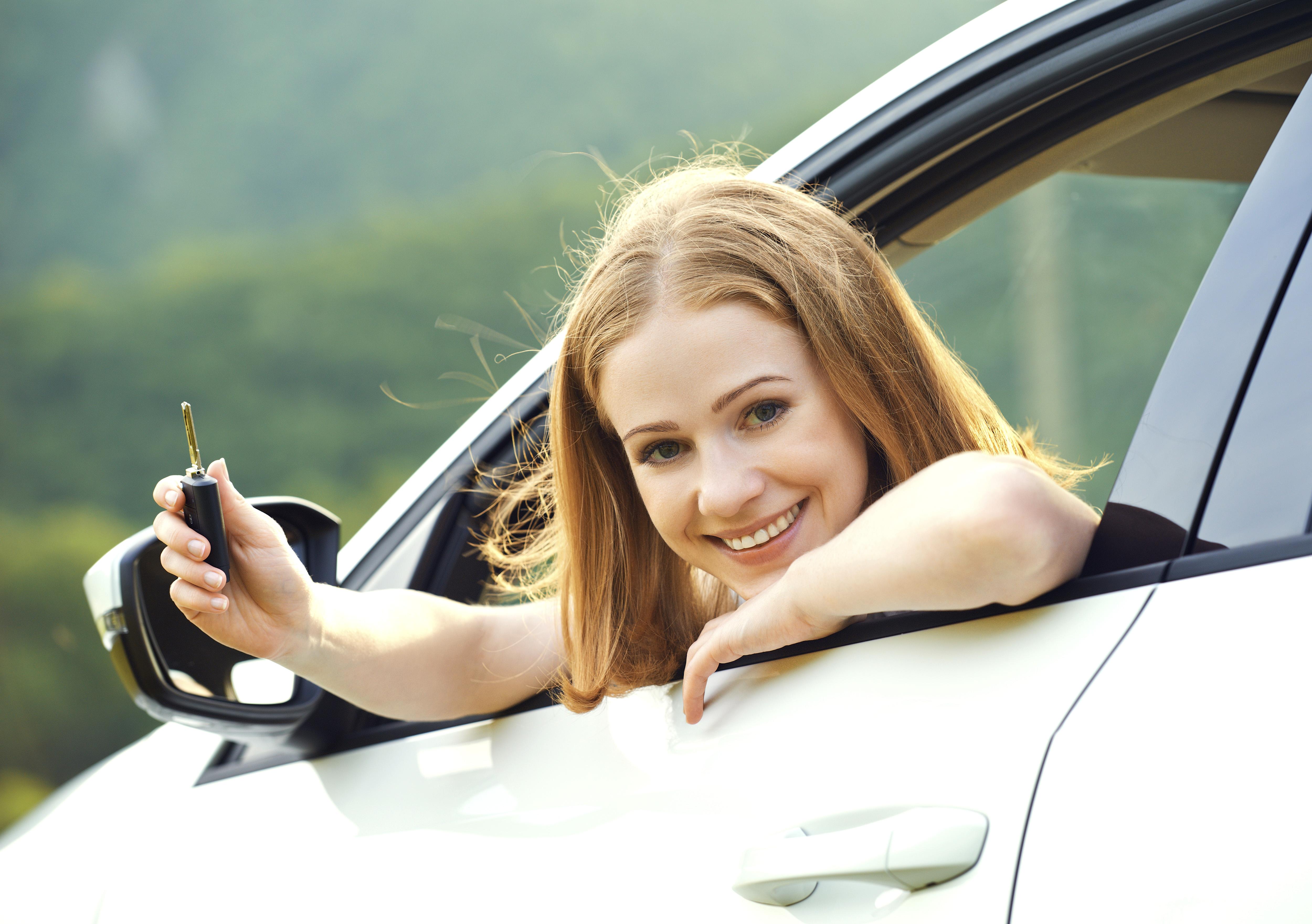 Lächelnde Frau am Steuer lehnt sich aus dem Autofenster mit Autoschlüssel in der Hand