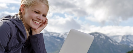 Frau mit Laptop in den Alpen