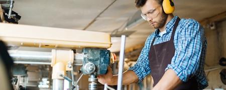 Junger Zimmermann bei der Arbeit an der Standbohrmaschine
