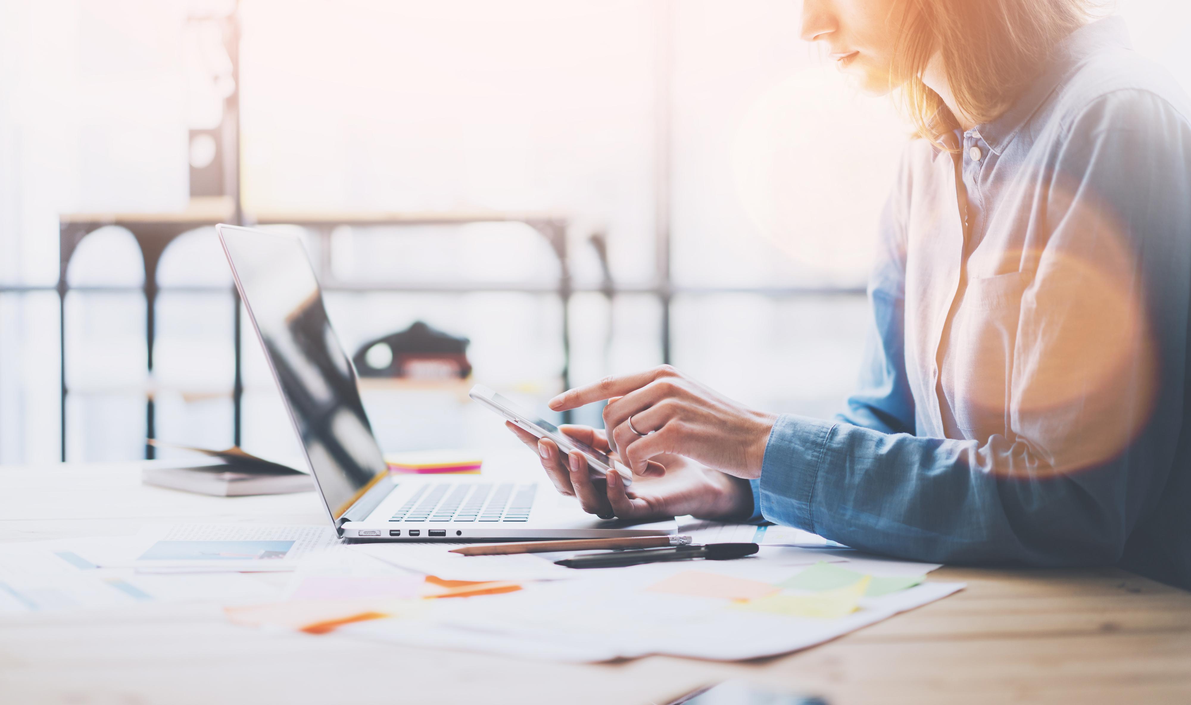 Frau am Arbeitsplatz mit Smartphone und Laptop