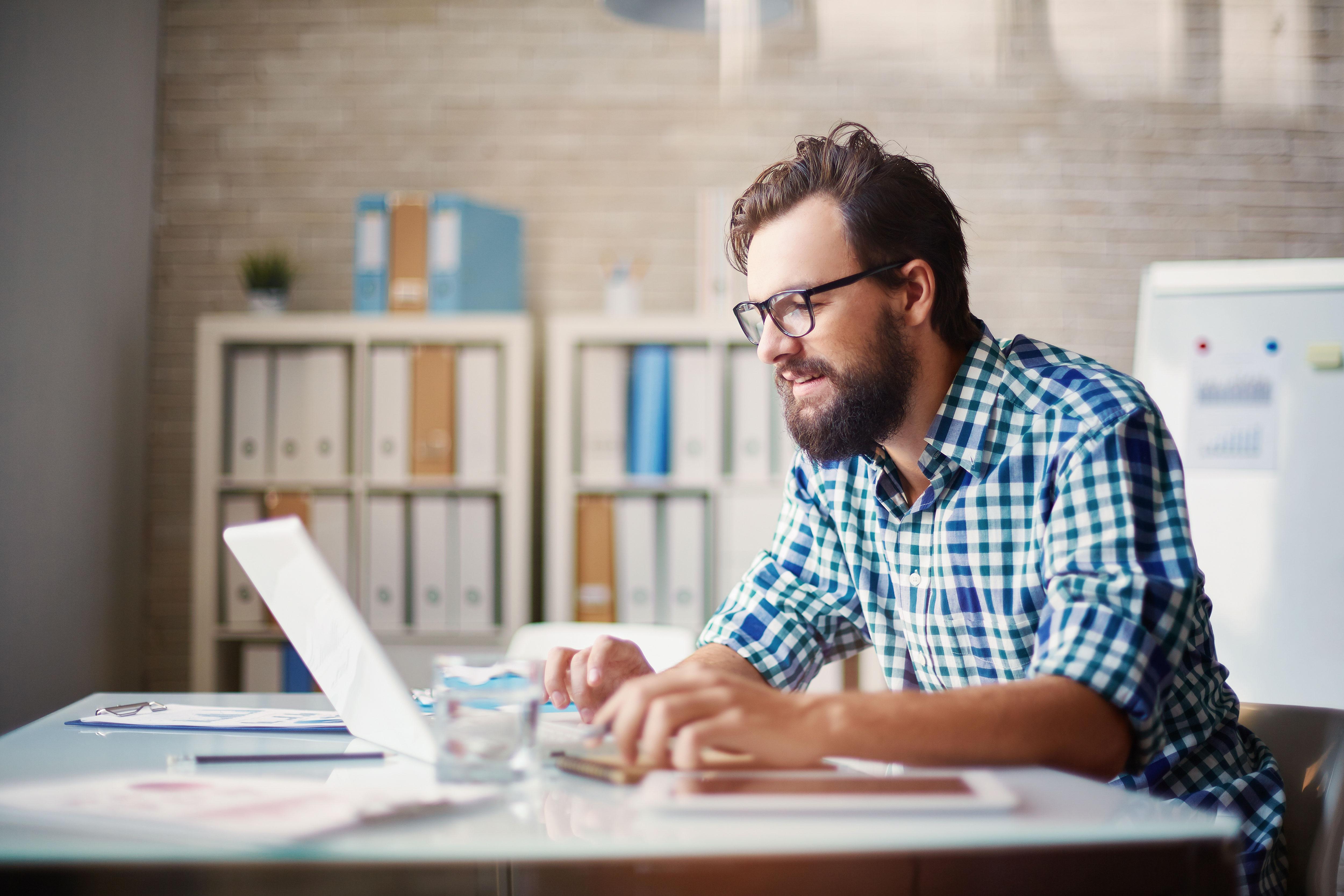 Mann tippt etwas auf einem Laptop