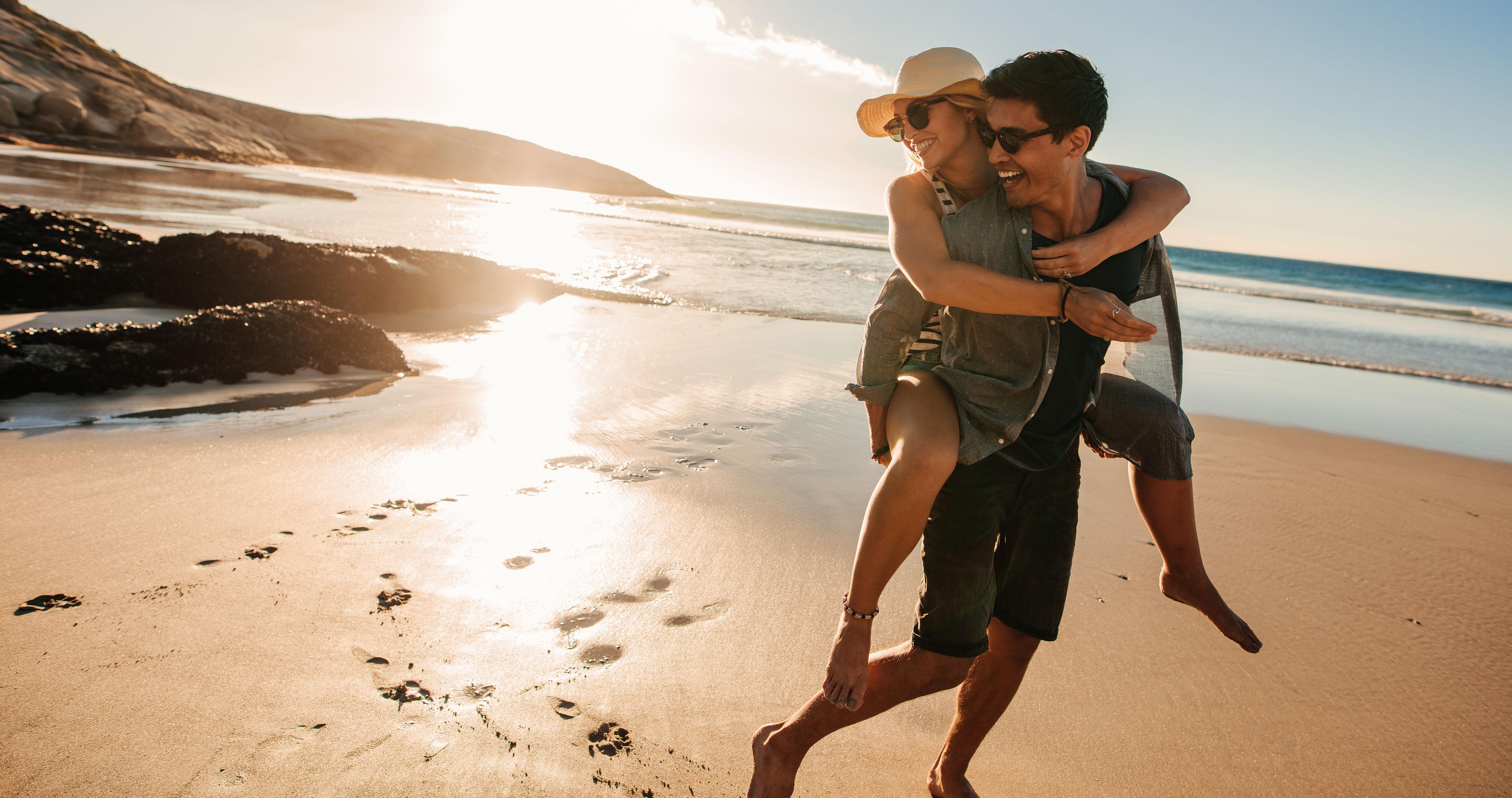 Mann läuft Huckepack mit seiner Freundin am Strand
