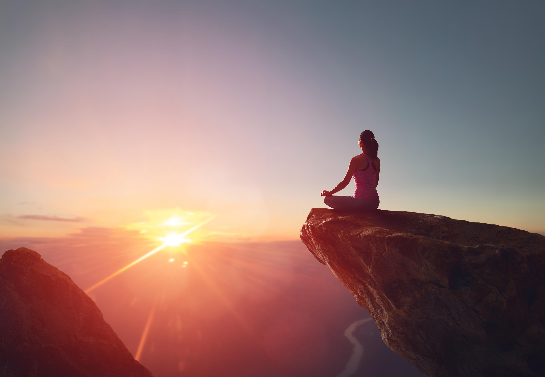 Frau in Yogapose auf Felsvorsprung im Sonnenuntergang