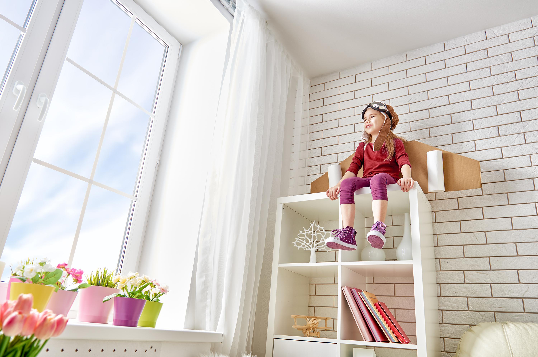 Junges Mädchen spielt im Astronautenkostuem und sitzt auf einem Regal.