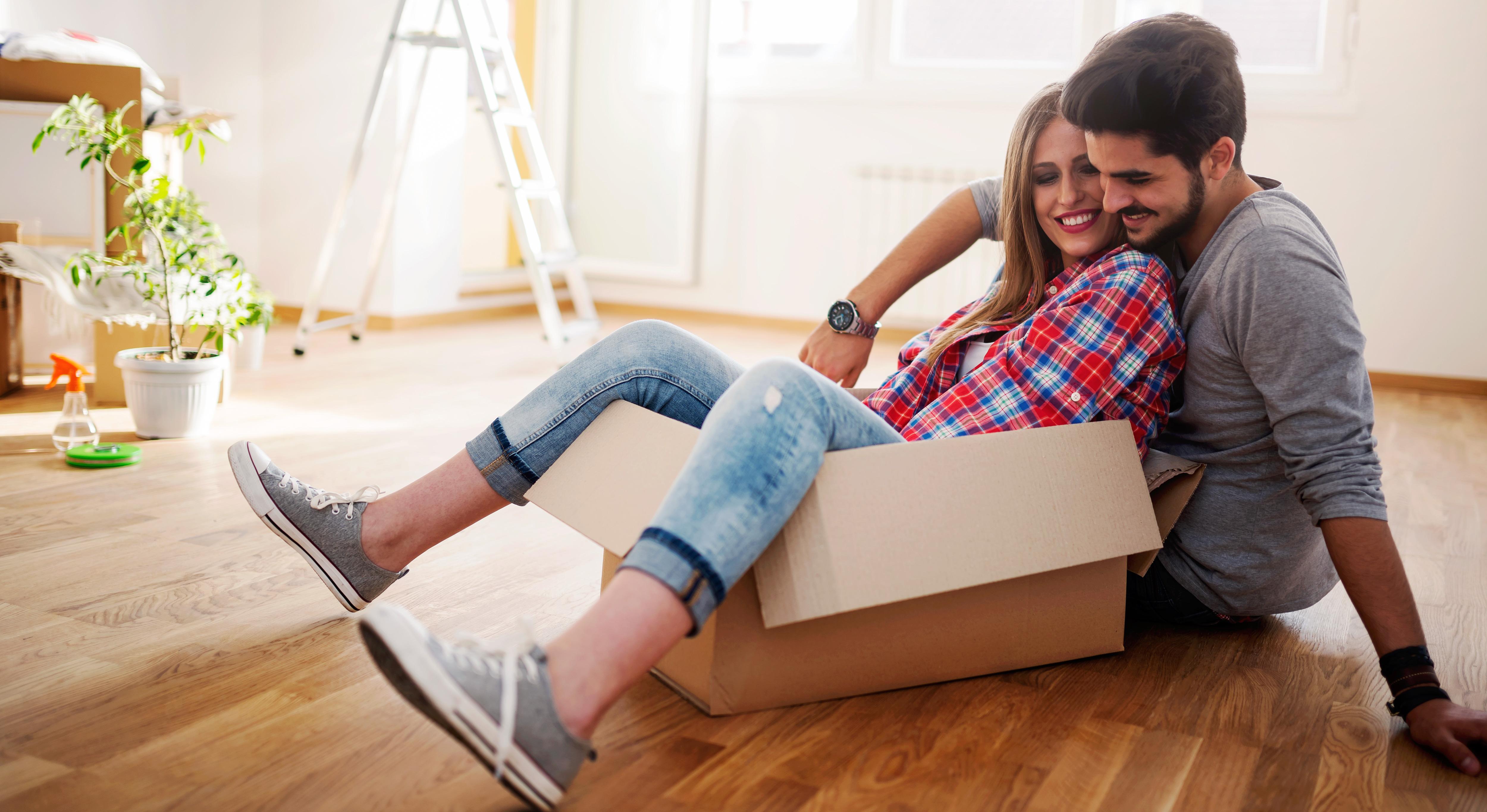 Glückliches junges Paar mit Umzugskarton in der neuen Wohnung