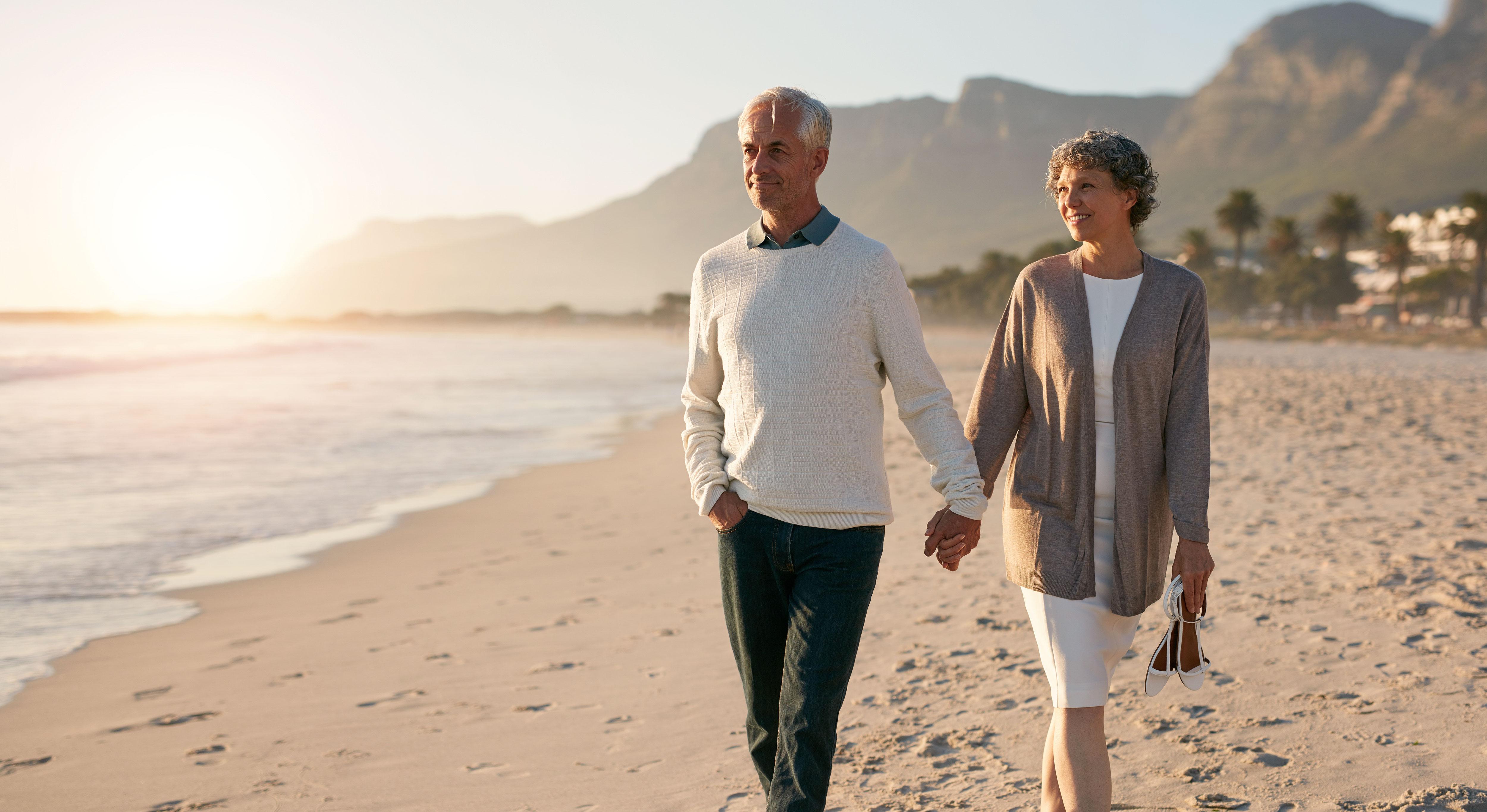 Seniorenpaar spaziert entspannt am Strand