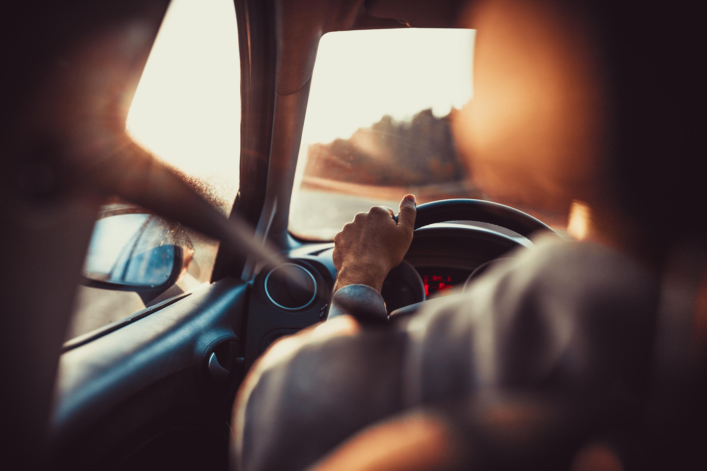 Mann fährt Auto, Hand am Lenkrad und schaut auf die Straße voraus, Sonnenuntergang.