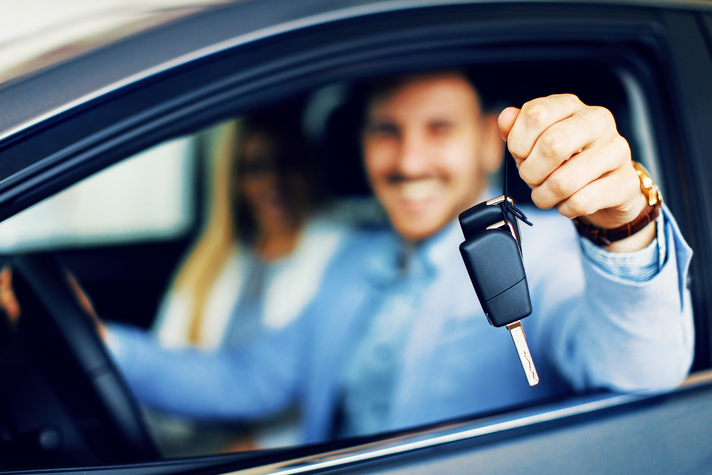 Junges Paar hält die Schlüssel eines neuen Autos in der Hand.