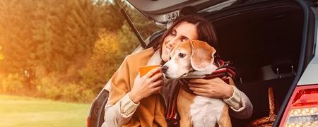 Frau sitzt mit Hund im Kofferraum