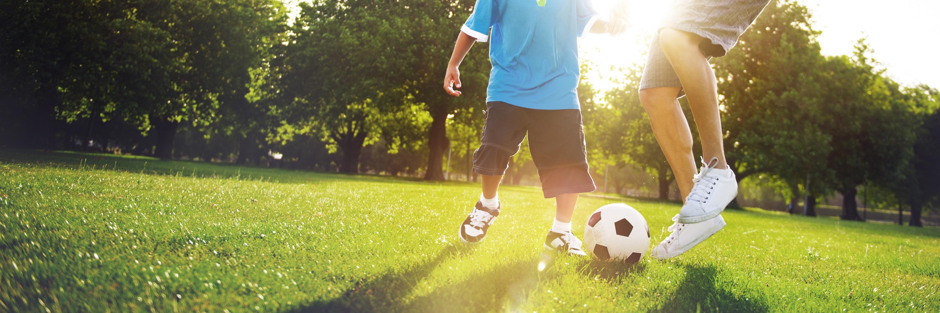 Kleiner Junge spielt mit seinem Vater Fußball.