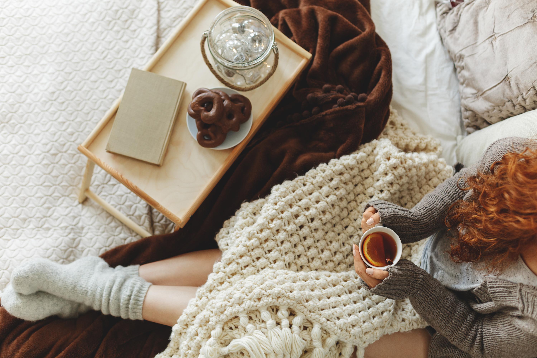 Junge Frau mit der Teetasse in den Händen beim Frühstück im Bett