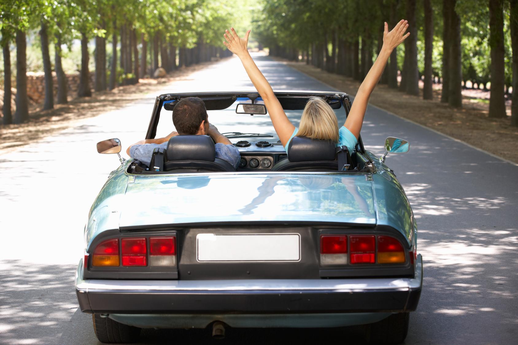 Paar in Cabrio auf einer Allee